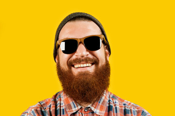 Portrait of young hipster man in sunglasses and hat posing on yellow background. Smiling bearded man wearing sunglasses and looking confident at the camera, studio shot.