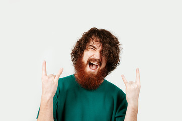 Handsome bearded man with long curly hair showing the symbol of rock and roll / heavy metal rock over white background