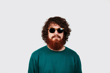 Portrait of hipster guy with curly hair wearing sunglases looking at the camera. fashion bearded male model posing isolated over white background.
