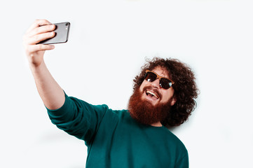 Smiling happy hipster man in sun glasses with beard standing on white isolated background and taking selfie with mobile phone.