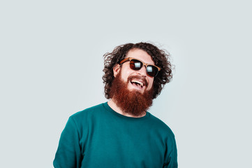 Portrait of cheerful bearded hipster man with long curly hair waring sunglasses and smiling over white background