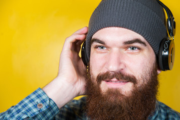 Close up portrait of young man with beard listen music at headphones in studio. Bearded hipster listen music.