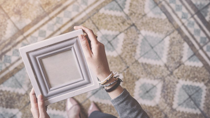 Wall Mural - Young woman holding photo frame