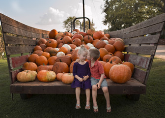 Brother kissing sister while sitting against pumpkins on cart