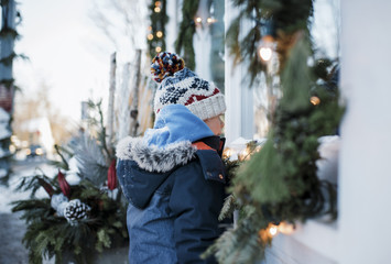 Side view of boy in warm clothing standing by house