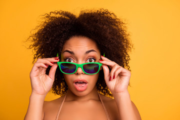 What are you talking about? Cropped close up portrait of surprised funny emotional face expression of beautiful afro with bronze tanned skin fluffy brown hair woman, isolated on yellow background