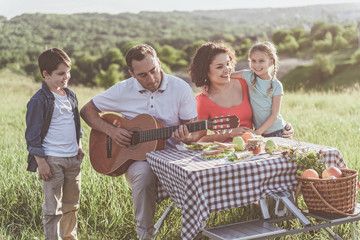Happy family are having fun on picnic in the nature. Father is playing guitar while his son listening to music attentively. Mother and daughter are embracing and laughing