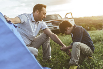 Joyful father is teaching his son to pitch a tent. Boy is holding a rope with interest while kneeling on grass