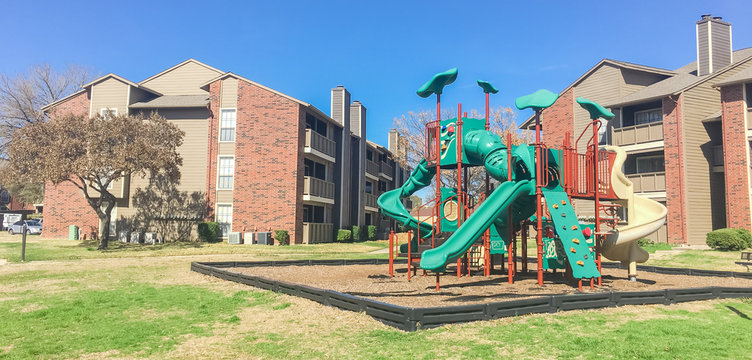 A typical apartment complex building with a central playground swing, stairs in suburban area at Irving, Texas, US. View from grassy backyard under clear blue sky. Panorama view