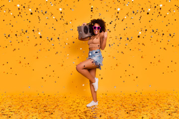 Turn the volume up! Full-length of cool crazy brash restless sleepless swag noisy mulato woman wearing star glasses knitted top, holding stereo record player on shoulder, isolated on yellow background