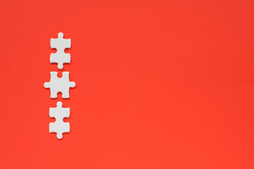 Wall Mural - three white details of puzzle on red background