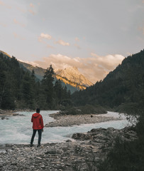 Hiker looking at view while standing by river against mountains