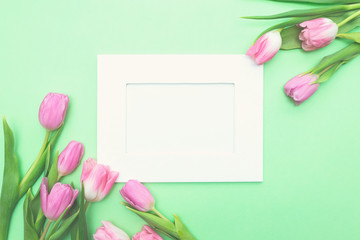 Top view of pink tulips and photo frame on light green background with copy space. Beautiful spring background for International Womens day, Mother's day, March 8, Valentines day