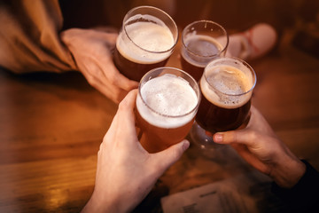 Papiers peints Biere, Cidre friends clinking and toasting with delicious craft beer in bar. group of people cheering and enjoying a beer in pub. hands holding glasses of beer. leisure and friendship concept