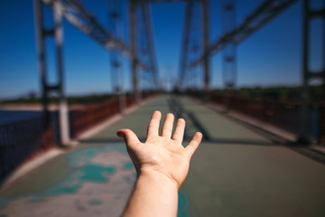 man hand on background of steel bridge in city. summer travel concept. sport destination