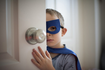 Close up of boy in superhero costume while standing by the door at home