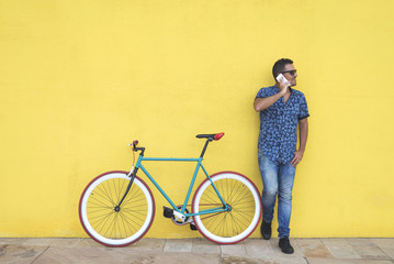 Man talking on smart phone while standing by bicycle against yellow wall at sidewalk in city