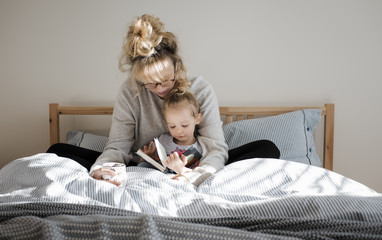 Mother with daughter reading book while sitting on bed at home