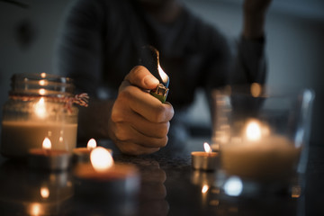 Midsection of man igniting candles with cigarette lighter on table in darkroom