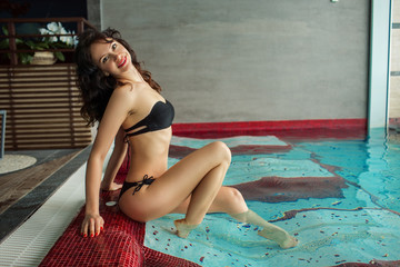 Pretty young flexible woman is relaxing in swimming pool in spa complex, health resort concept