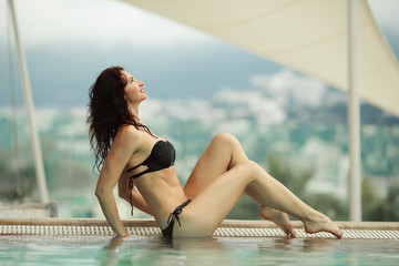 Beautiful young woman is relaxing in openair swimming pool in spa complex over mountains view