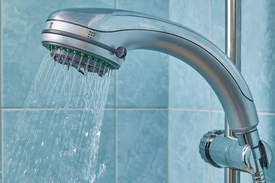 Water flows from shower head, fixed in holder inside bathroom.