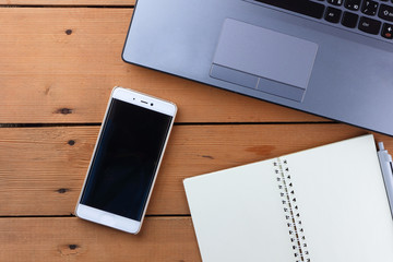 Laptop on a wooden background, a job on an old table, smartphone and notebook, pen and glasses in the workplace, copy space, office space in a minimalist style