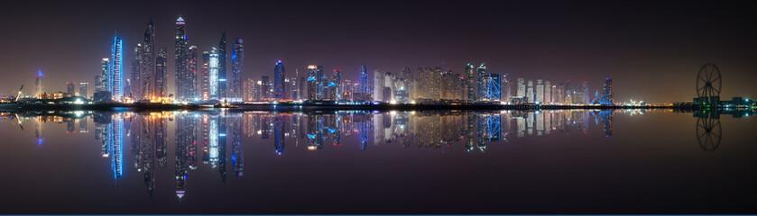 Panoramic view of Dubai Marina skyline with reflection at night, UAE