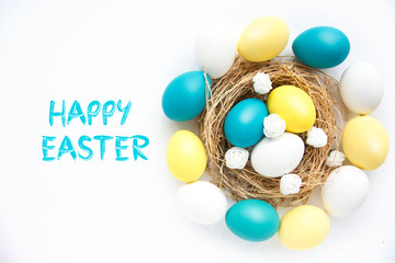 colored blue and yellow Easter eggs in nest on wooden background, selective focus image. Happy Easter card