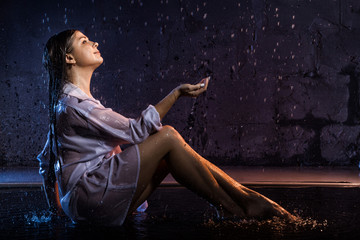 Girl in the white shirt with water drops and dark walls background illuminated by light during a photoshoot with water