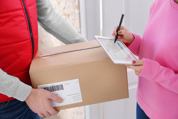 Woman signing on tablet for parcel delivery, closeup