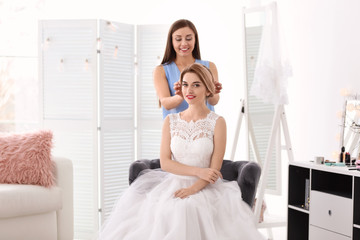 Fashion stylist preparing bride before her wedding indoors
