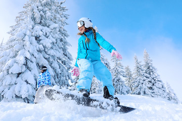 Female snowboarder on ski piste at snowy resort. Winter vacation