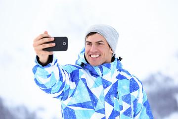Happy man taking selfie outdoors. Winter vacation