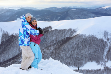 Happy couple on snowy mountain peak at resort. Winter vacation