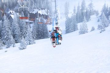 Couple on ski lift at mountain resort. Winter vacation