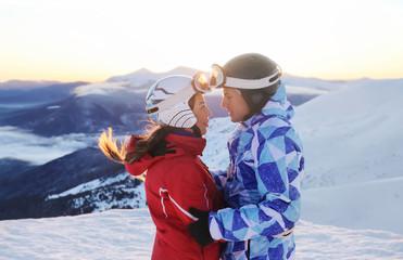 Happy couple on snowy peak at ski resort. Winter vacation