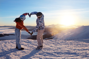 Lovely couple holding hands in shape of heart on snowy peak at sunset. Winter vacation