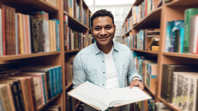 Ethnic indian mixed race student in book aisle of library.