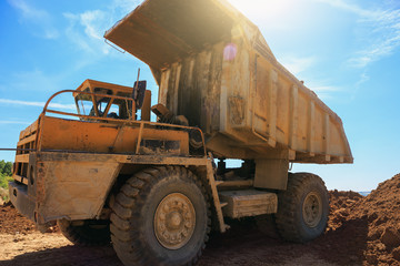 Big yellow mining truck at quarry at blue sky background