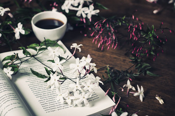 jasmine flowers, open book and a cup of coffee on a wooden table
