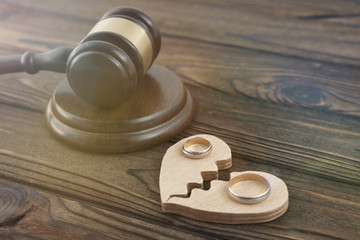 two wedding rings, a heart, a judge hammer on a wooden background. family law