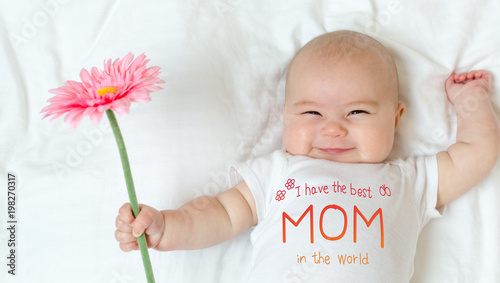 Mother's Day message with baby girl holding a flower