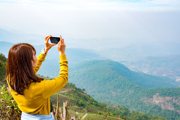 Travelers enjoy nature photography with a smartphone.