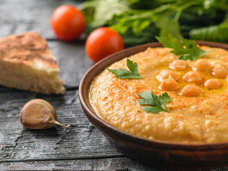 Freshly made hummus in a clay bowl on a table with a piece of bread.