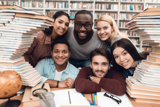 Six ethnic students, mixed race, indian, asian, african american and white surrounded with books at library.