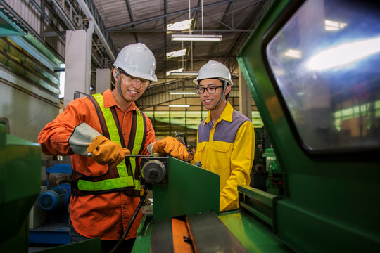 Asian engineer and worker setting machine for process metal job