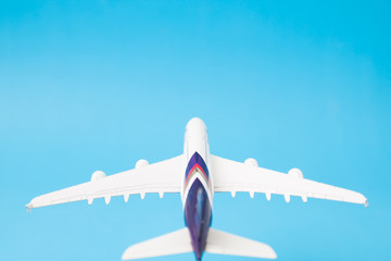 Creative flat lay of travel comcept with airplane on blue color background with copy space