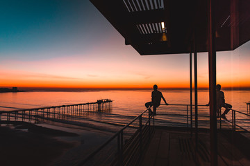 Silhouette of men sitting on pier railing and watching sunset