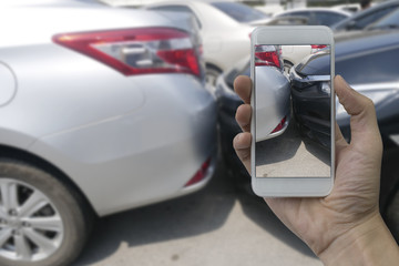 Hand holding smart phone take a photo at The scene of a car crash